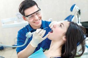 leende läkartandläkare behandlar tänder. le kvinnlig patient sitter foto