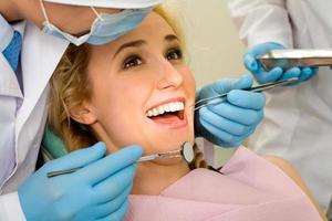 en ung kvinna omgiven av tandläkare i tandläkaren foto