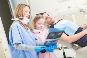 små tandläkare tittar på röntgen av vuxen patient foto