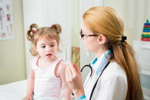 barnläkare som ger medicin till liten flicka foto