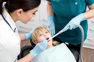 tandläkare behandla en liten flicka foto