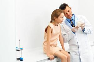 tandläkare som visar en flicka hur man borstar tänderna. foto