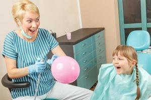 glad liten flicka hos tandläkaren foto