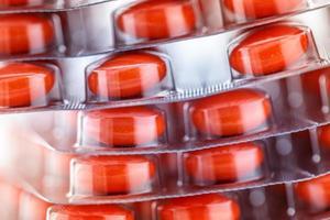 röda tabletter i plastförpackning foto