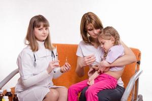 barnläkare kommer att få ett sköt sjukt barn sitter foto
