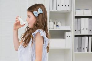 liten flicka som tar inhalator foto