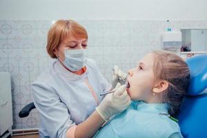 liten flicka som sitter på tandläkarkontoret foto