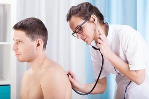 läkare auscultating patient foto