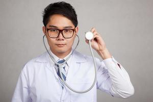 asiatisk manlig läkare med stetoskop foto