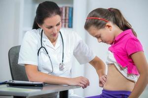 läkare som kontrollerar magen hos den sjuka flickan foto