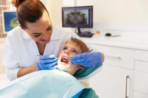 pojke besöker tandläkaren för en kontroll foto