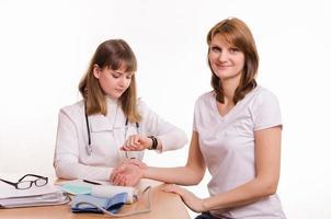 läkaren tar hänsyn till flickans puls vid skrivbordet på kontoret foto