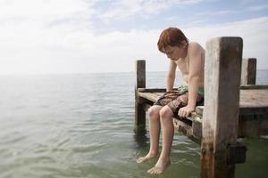 pre-teen pojke sitter på slutet av piren foto
