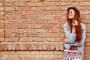 vacker söt tonåring tjej ler nära tegelväggen foto