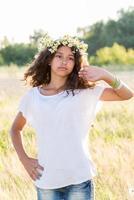 tonårig flicka med en krans av prästkragar i fältet foto