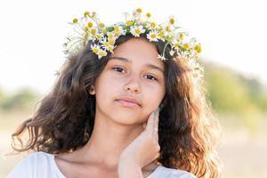 tonårig tjej med en krans av prästkragar i fältet foto