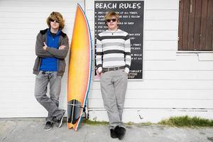 tonårspojkar med surfbräda foto