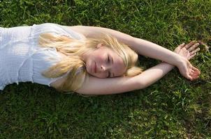 tonårsflicka som ligger i gräset foto