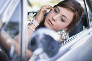 tonårsflicka som kontrollerar smink i bilen foto