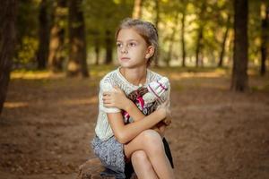 charmig liten flicka i skogen med dockan foto
