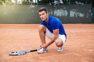 manlig tennisspelare som knyter skosnören foto