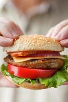 läcker hamburgare i manliga händer foto