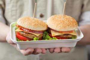behållare med hamburgare i manliga händer foto