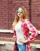 porträtt ung flicka klädd i en rutig skjorta och solglasögon ove foto