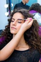 kvinna att sätta mascara smink foto