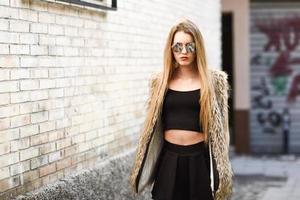 blond flicka som ler i urban bakgrund foto