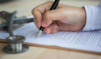 hand av läkare som skriver på recept foto