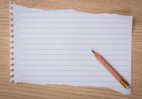 vitt anteckningsbokpapper med penna på ett träskrivbord foto