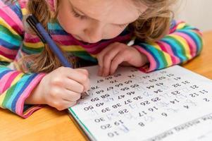 närbild av en ung flicka som slutför matematikläxor foto