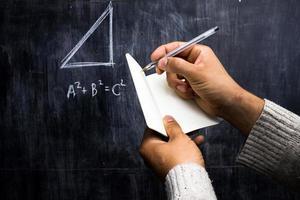 man tar anteckningar av matematiska teorem på tavlan