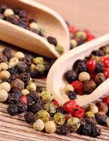 färsk färgad peppar med sked på träbakgrund foto