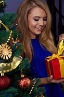 kvinna under nyårsträd med julklapp foto