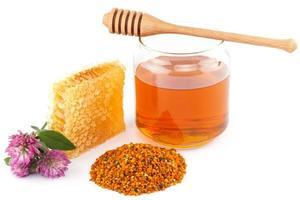 honung i burken med skopa, honungskaka, pollen och blommor foto