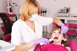 liten flicka patient och tandläkare foto