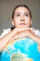drömmer om framtiden. flicka med blå jordklot. foto