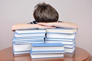 trött ung pojke och böcker foto