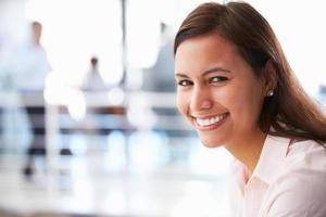 porträtt av kvinna i office ler mot kameran foto