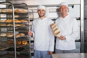 leende kollegor som håller färska bröd foto
