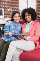 tillfälliga kollegor som använder digital tablet på soffan foto