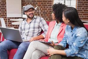 unga tillfälliga kollegor som använder bärbar dator på soffan foto