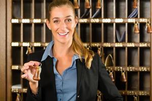 mottagning av hotell - kvinna som håller nyckeln i handen foto