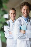 glada läkare stående armar korsade foto