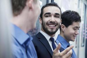 tre affärsmän som står i rad och pratar i tunnelbanan