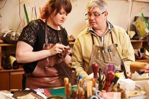 äldre skomakare utbildar lärling för att arbeta med läder foto