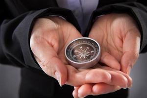 affärsman som håller kompass foto