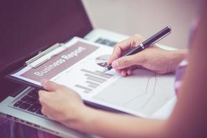 ung affärskvinna som hyvlar, skriver och granskar rapport på ci foto